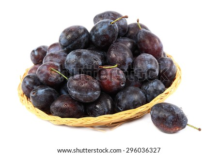 Fresh plums in a basket isolated on a white background. - stock photo
