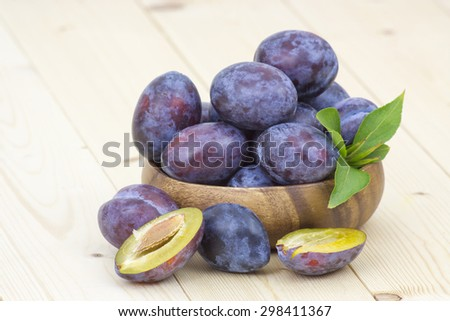 fresh plums in a bowl on wooden background - stock photo