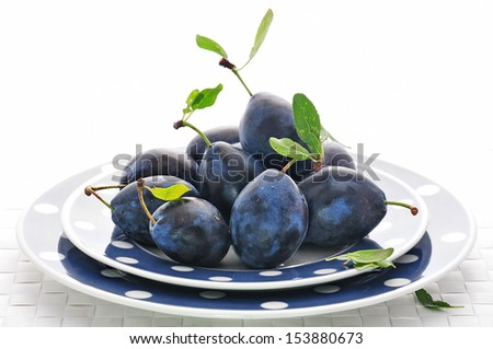 Fresh plums in bright plates - stock photo
