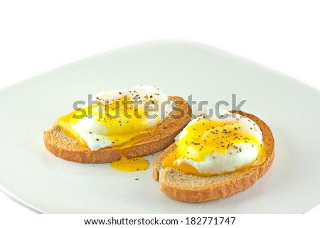 Fresh poached eggs on rye toast with a white background. - stock photo