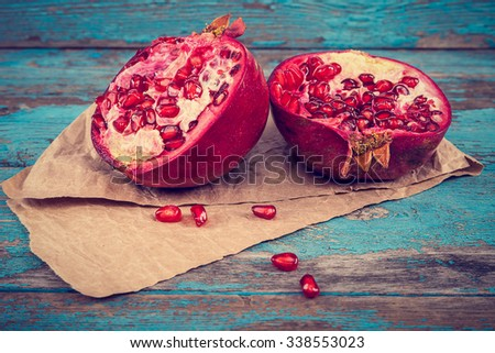 Fresh pomegranate on painted blue wooden boards. - stock photo