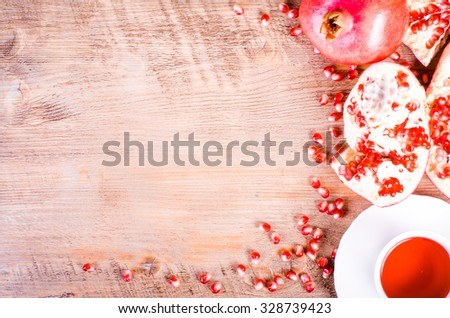 Fresh pomegranate seeds and cup of  hibiscus tea on wooden background.  - stock photo