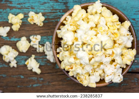 Fresh popcorn in bowl on white wooden table. Selective focus.  - stock photo