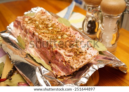 Fresh pork ribs, meat marinated and prepared for roast with garlic in a foil - stock photo