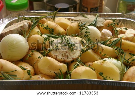 ... potato with garlic,onion,thyme and rosemary in a pan - stock photo