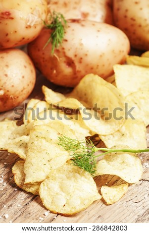 Fresh potatoes and potato chips on an old wooden table, selective focus - stock photo