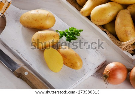 Fresh potatoes on a white wooden cutting board - stock photo