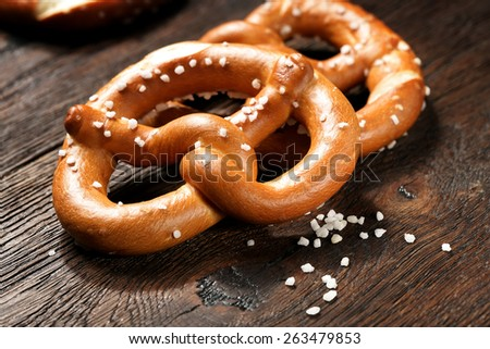 Fresh pretzels with sea salt close-up on  dark board background  - stock photo