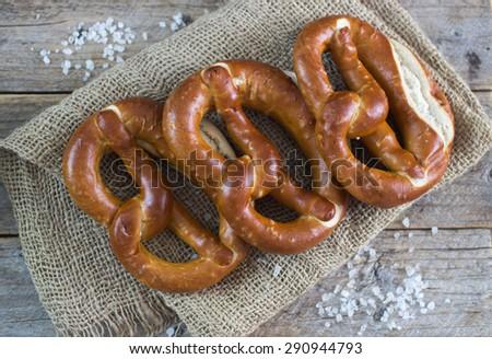 Fresh pretzels with sea salt on wooden table - stock photo
