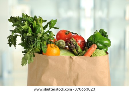 Fresh produce in paper grocery bag inside kitchen - stock photo