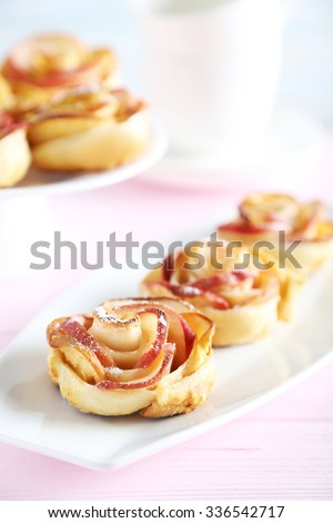 Fresh puff pastry with apple shaped roses on pink wooden table - stock photo