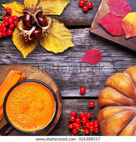 Fresh pumpkin and carrot juice on wooden background in autumn season   - stock photo
