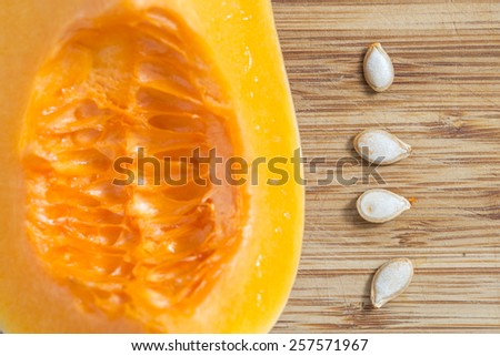 Fresh pumpkin cutting in quarter and four seeds on a bamboo board. on a bamboo board. - stock photo