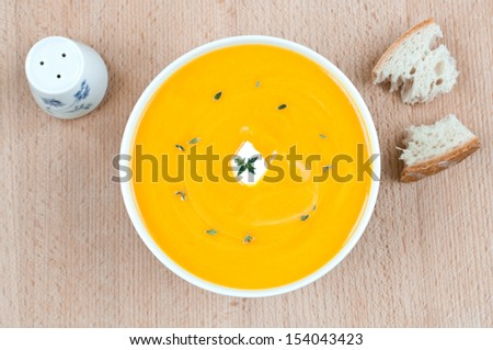 Fresh pumpkin soup in white bowl with thyme on top with bread and salt cellar - stock photo
