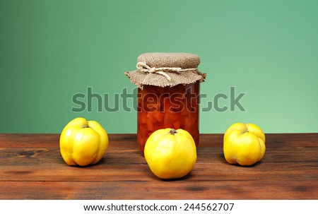 Fresh quince jam in a jar and glass on the table - stock photo