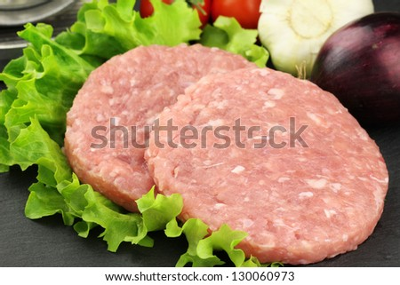 Fresh rabbit burgers on a leaf of lettuce with onion and garlic at the background - stock photo
