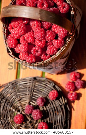fresh raspberry in a basket on wooden table sunlight - stock photo
