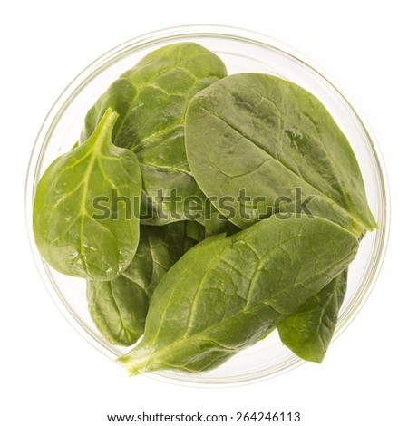 Fresh raw baby spinach leaves in glass bowl, isolated on white and viewed from directly above. - stock photo