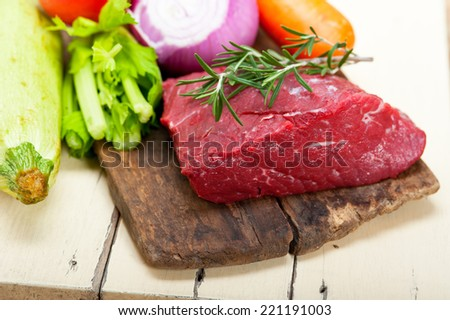 fresh raw beef cut ready to cook with vegetables and herbs - stock photo
