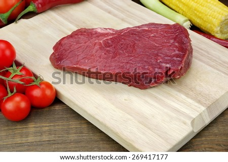 Fresh Raw Beef Fillet Loin Steak And Vegetables On Wood Cutting Board Background - stock photo