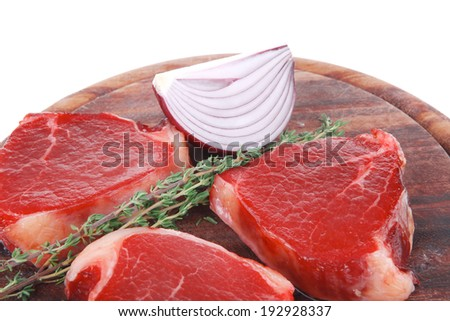 fresh raw beef fillet medallions with thyme twig on wooden plate isolated over white background - stock photo
