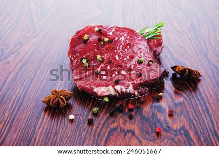 fresh raw beef fillet mignon on old retro style wood as background with rosemary peppercorn and salt - stock photo