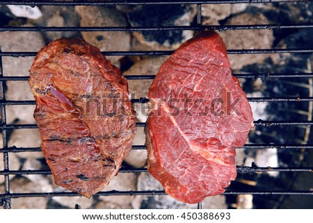 fresh raw beef fillet steak red meat on big round barbecue brazier black grid full burned charcoal - stock photo