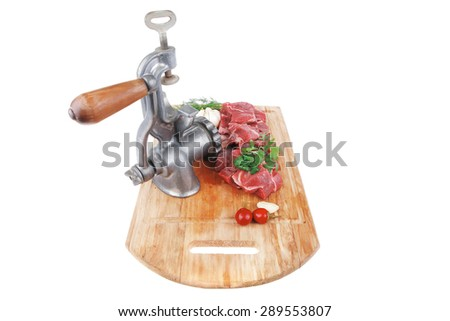 fresh raw beef meat slices over a wooden board with dill , green  and red hot peppers, and grinder isolated over white background - stock photo