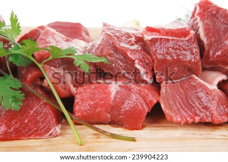 fresh raw beef meat slices over a wooden board with dill , green  and red hot peppers isolated over white background - stock photo