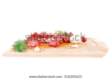 fresh raw beef meat slices over a wooden board with dill , green  and red hot peppers isolated over white backkground - stock photo