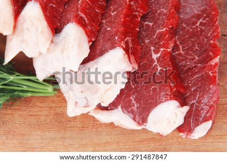 fresh raw beef meat steak slices on wooden cut board isolated over white background - stock photo