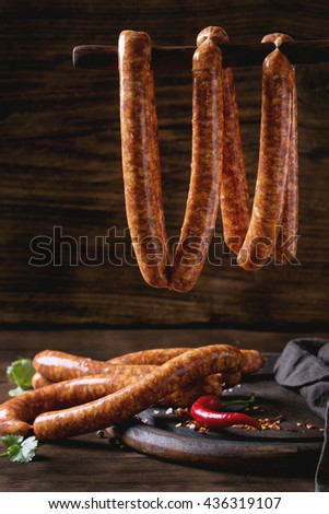 Fresh raw beef sausages with spices for BBQ hanging on stick over dark wooden background with salt, herbs and pepper.  - stock photo