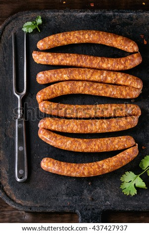 Fresh raw beef sausages with spices for BBQ on black iron board over dark wooden background with salt, herbs, pepper and big meat fork. Top view.  - stock photo