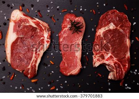 Fresh, raw beef steak on a black stone tray - stock photo