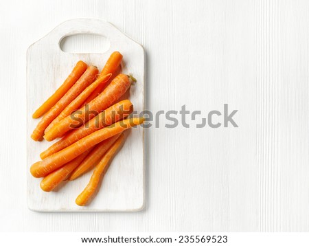 fresh raw carrots on white wooden table - stock photo