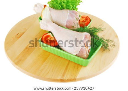 fresh raw chicken drumstick in green bowl ready to be baked on wooden plate isolated over white background with green lettuce salad and tomatoes - stock photo