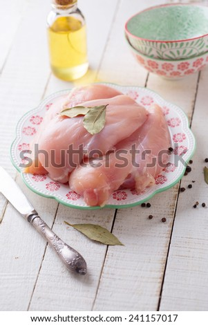 Fresh raw chicken meat on plate on white table with bay leaves, oil. Selective focus. - stock photo