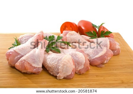 Fresh raw chicken wings on chopping board with roma tomatoes - stock photo