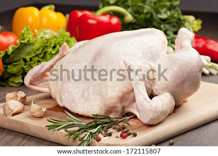 Fresh raw chicken with spices and a sprig of rosemary  on the background of vegetables - stock photo