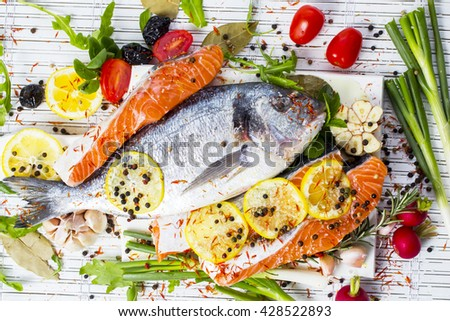 Fresh raw gilthead fishes and salmon with lemon, herbs, salt on a wooden board , white wooden background. Healthy food concept. Food frame.Fish bream - stock photo