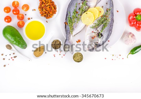 Fresh raw gilthead fishes with lemon, herbs, olive oil, avocado, paprika, ?herry tomatoes, garlic, salt on white background. Healthy food concept. Food frame. Free space for your text - stock photo