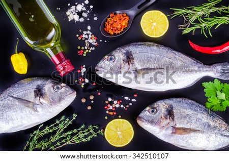 Fresh raw gilthead fishes with lemon, herbs, salt on black background. Healthy food concept. Food frame - stock photo