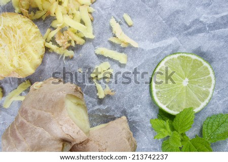 Fresh raw ginger with grated pieces and lime and mint - stock photo