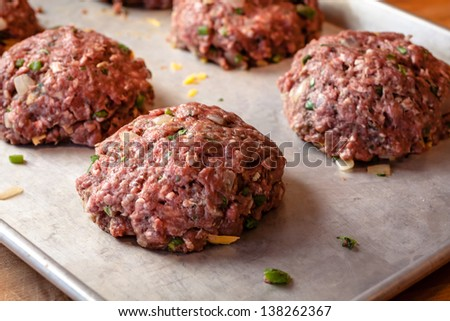 Fresh raw ground beef gourmet burgers sitting on pan, ready to be cooked - stock photo