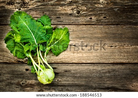 Fresh Raw Kohlrabi Vegetables With the Leaves On A Rustic Wood Background  - stock photo