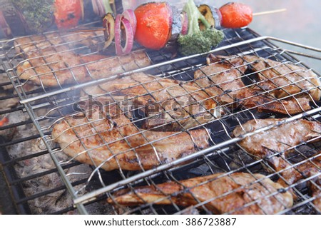 fresh raw lamb ribs on meat holder over fire burned churcoal with vegetable shish kebab on side outdoor party - stock photo