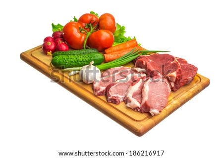 Fresh raw meat and vegetables on a cutting board - stock photo