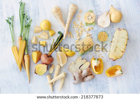 Fresh raw organic food displayed in an overhead shot carrot pineapple parsnip corn golden beetroot capsicum - stock photo