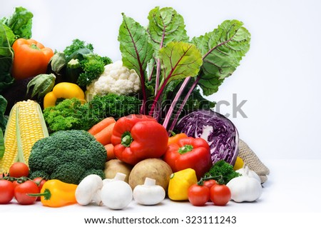 Fresh raw organic vegetable produce, assortment of corn, peppers, broccoli, mushrooms, beets, cabbage, parsley, tomatoes, isolated on light background - stock photo