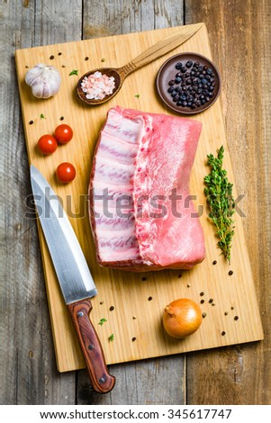 Fresh raw pork chop meat, chef knife, spices, vegetables and herbs on wooden cutting board background, top view - stock photo